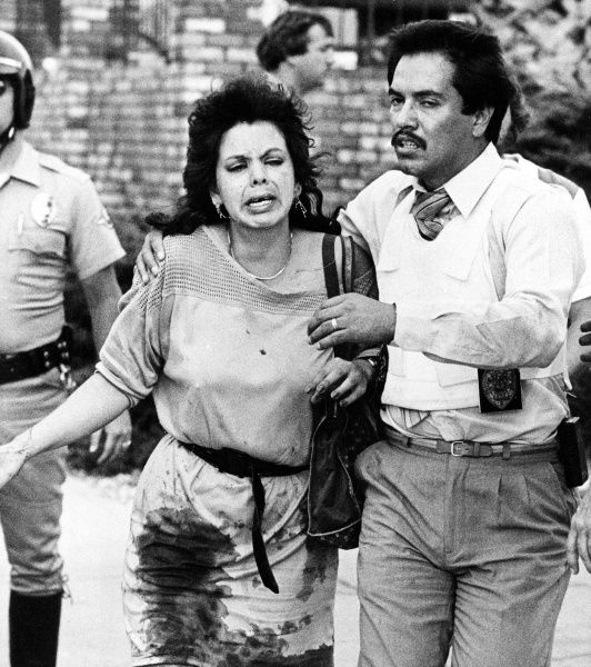 A police officer leads a bloodied woman away from the scene of a shooting rampage on July 18, 1984, at a McDonald's restaurant in San Diego, Calif. James Oliver Huberty shot and killed 21 people -- including five children and six teens -- and wounded 19, before being killed by a police sniper.