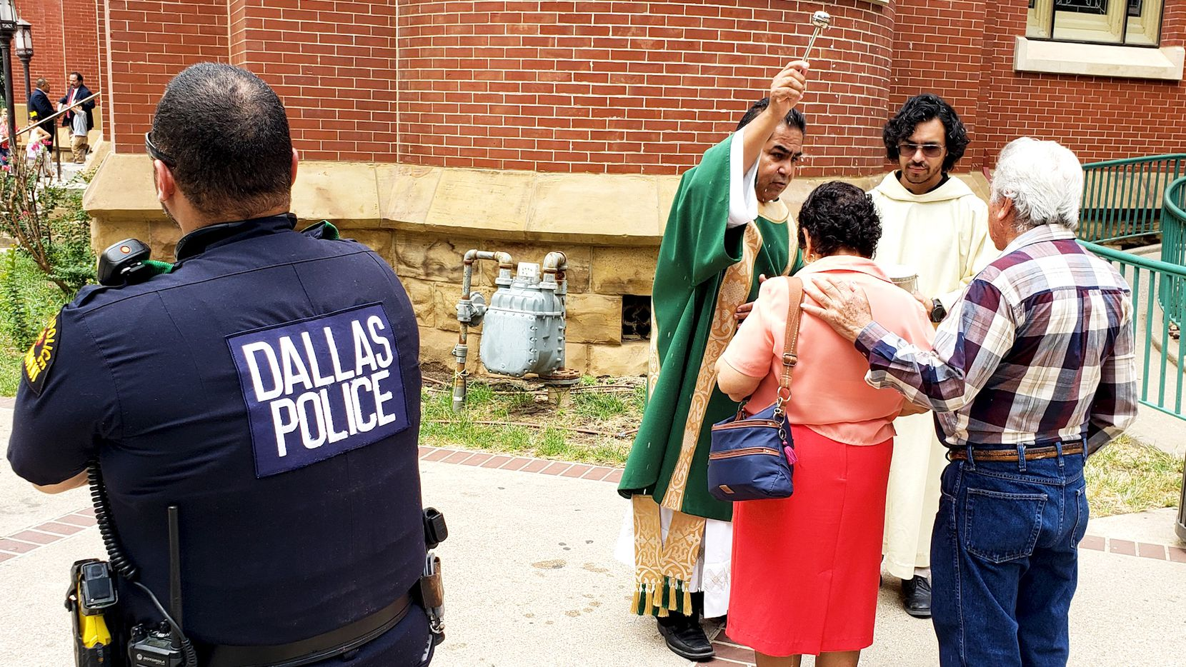 Deacon Roberto Alvarez and Raul Rodriguez bless a couple with holy water Sunday as Dallas police Officer Anthony Colon watches at the Cathedral Shrine of the Virgin of Guadalupe. Extra security measures were in place at the church a day after a massacre at a Walmart in El Paso.