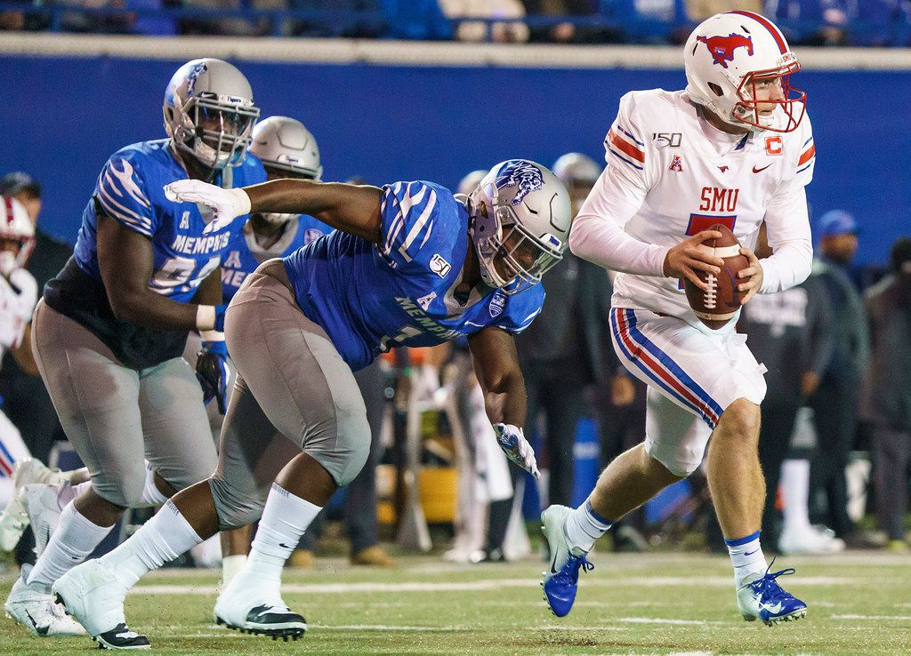 SMU quarterback Shane Buechele (7) scrambles away from Memphis defensive lineman O'Bryan Goodson (1) during the first half of an NCAA football game at Liberty Bowl Memorial Stadium on Saturday, Nov. 2, 2019, in Memphis, Tenn. (Smiley N. Pool/The Dallas Morning News)