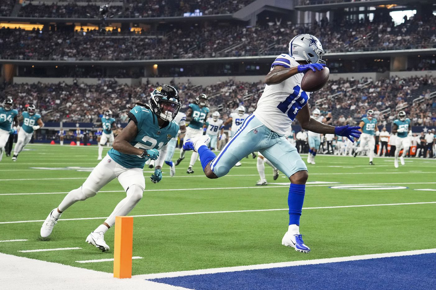 Dallas Cowboys wide receiver Aaron Parker (18) scores on a 19-yard touchdown  reception past Jacksonville Jaguars cornerback Sidney Jones (21) during the first half of a preseason NFL football game at AT&T Stadium on Sunday, Aug. 29, 2021, in Arlington. (Smiley N. Pool/The Dallas Morning News)