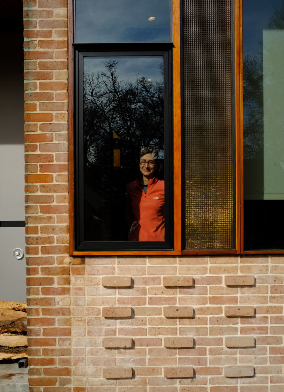 Lea Bauman in the front window of her house in Cochran Heights.