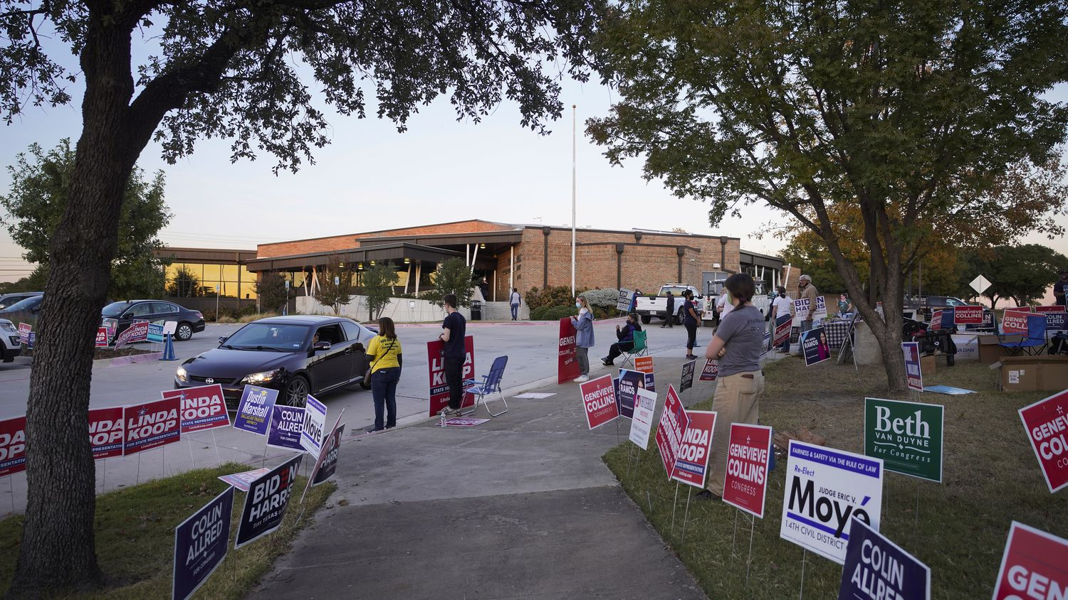 Supporters of various candidates greet voters outside a polling place at Fretz Park Branch Library on Election Day, Tuesday, Nov. 3, 2020, in Dallas.
