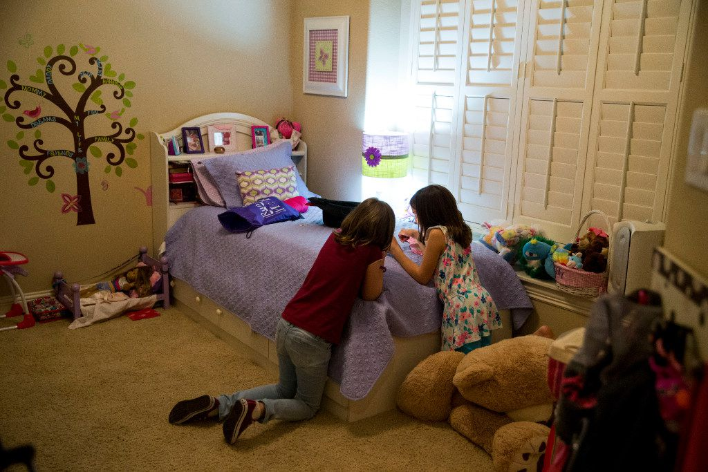 Julia Fischer (left), 10, of Brasília, Brazil, and Lily Howard, 8, bonds and spends time together communicating with language translating apps on smart phones at the Howard family home on Oct. 20, 2016 in The Colony, Texas. Both Fischer and Howard are older sisters who share a common experience taking care of an younger sister who's born with CDKL5, a rare genetic disorder that only affects roughly 600 people worldwide. (Ting Shen/The Dallas Morning News)