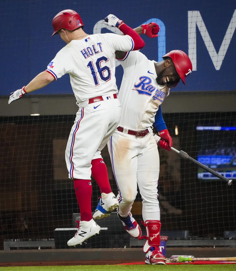Texas Rangers third baseman Brock Holt celebrates with center fielder Adolis Garcia after hitting a solo home run during the eighth inning against the Detroit Tigers at Globe Life Field on Tuesday, July 6, 2021. Garcia followed Holt with a homer of his own for back-to-back home runs in the inning.