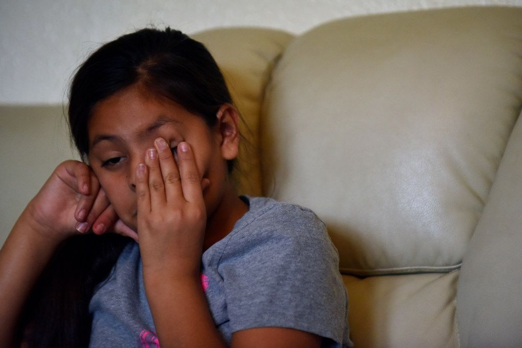 Amy Olguin, 10, rubs her eyes while listening to her mother speak about her father's death.