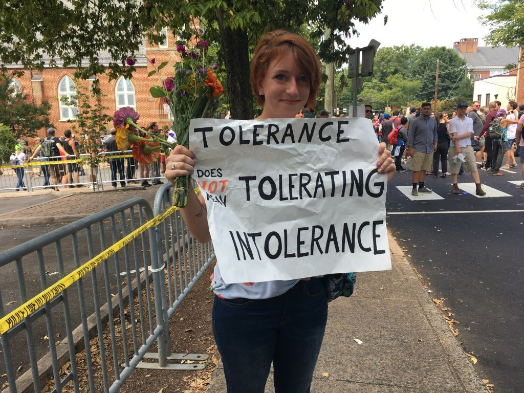 "Colleen Cook, 26, holds a sign as hundreds of people are facing off in Charlottesville, Va., ahead of a white nationalist rally planned in the Virginia city's downtown, Saturday, Aug. 12, 2017.   Cook, a teacher who attended UVA, said she sent her black son out of town for the weekend. ""This isn't how he should have to grow up,"" she said."