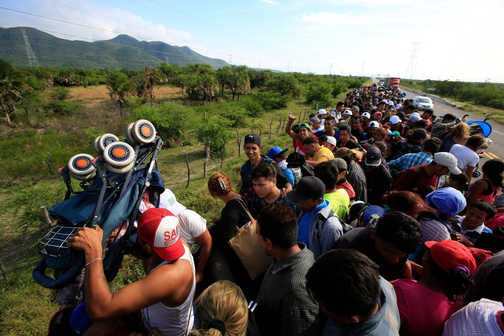A man holds up a stroller as hundreds of migrants hitching a ride accommodate themselves on the back of truck, between Niltepec and Juchitan, Mexico, on Oct. 30, 2018. The migrant caravan slowly advancing through southern Mexico is demanding that the Mexican government help its 4,000-some members reach Mexico City.