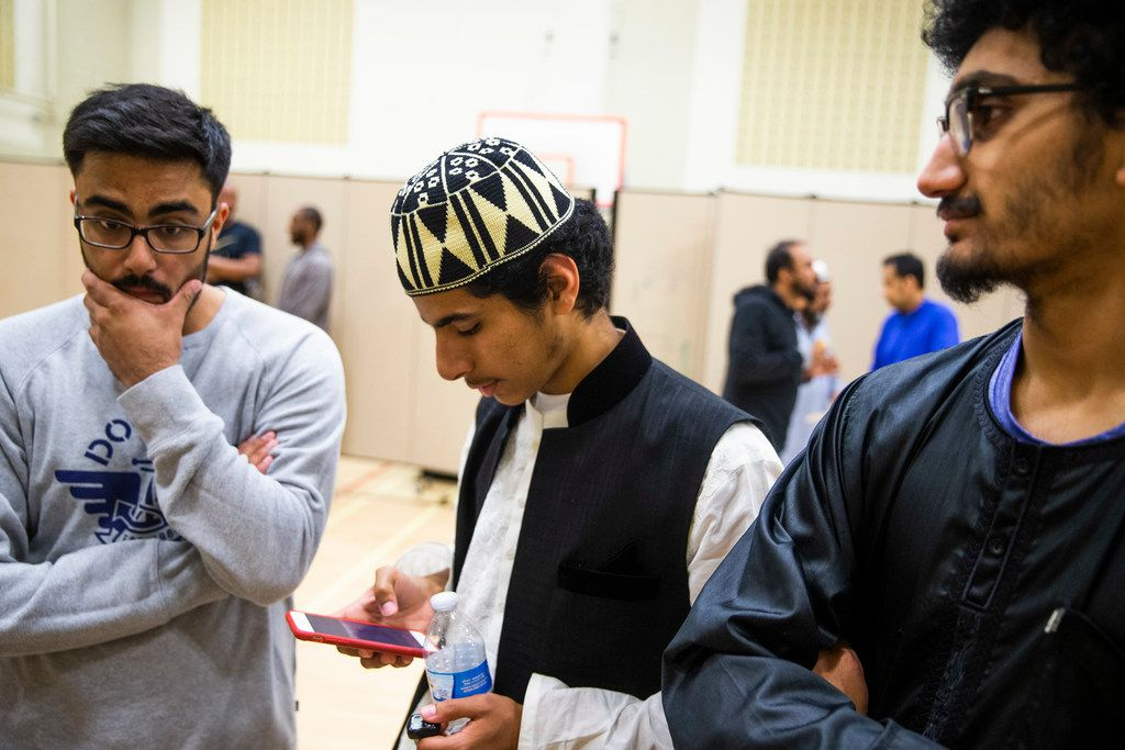 Hassaan Farooqi, middle, checks his phone as he makes plan for Suhur, a meal early in the morning before fasting, with Faaiz Nadeem, left, at Islamic Association of Collin County in Plano Texas Sunday, June 2, 2019. (Shaban Athuman/Staff Photographer)