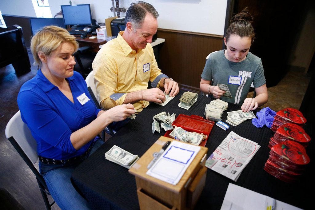Sarah Slack, (from left) Todd Garner and his daughter Christina Garner, 11, separate dollar bills in bundles of two to hand out after service at SoupMobile Church for the homeless in Dallas on Feb. 4, 2018.