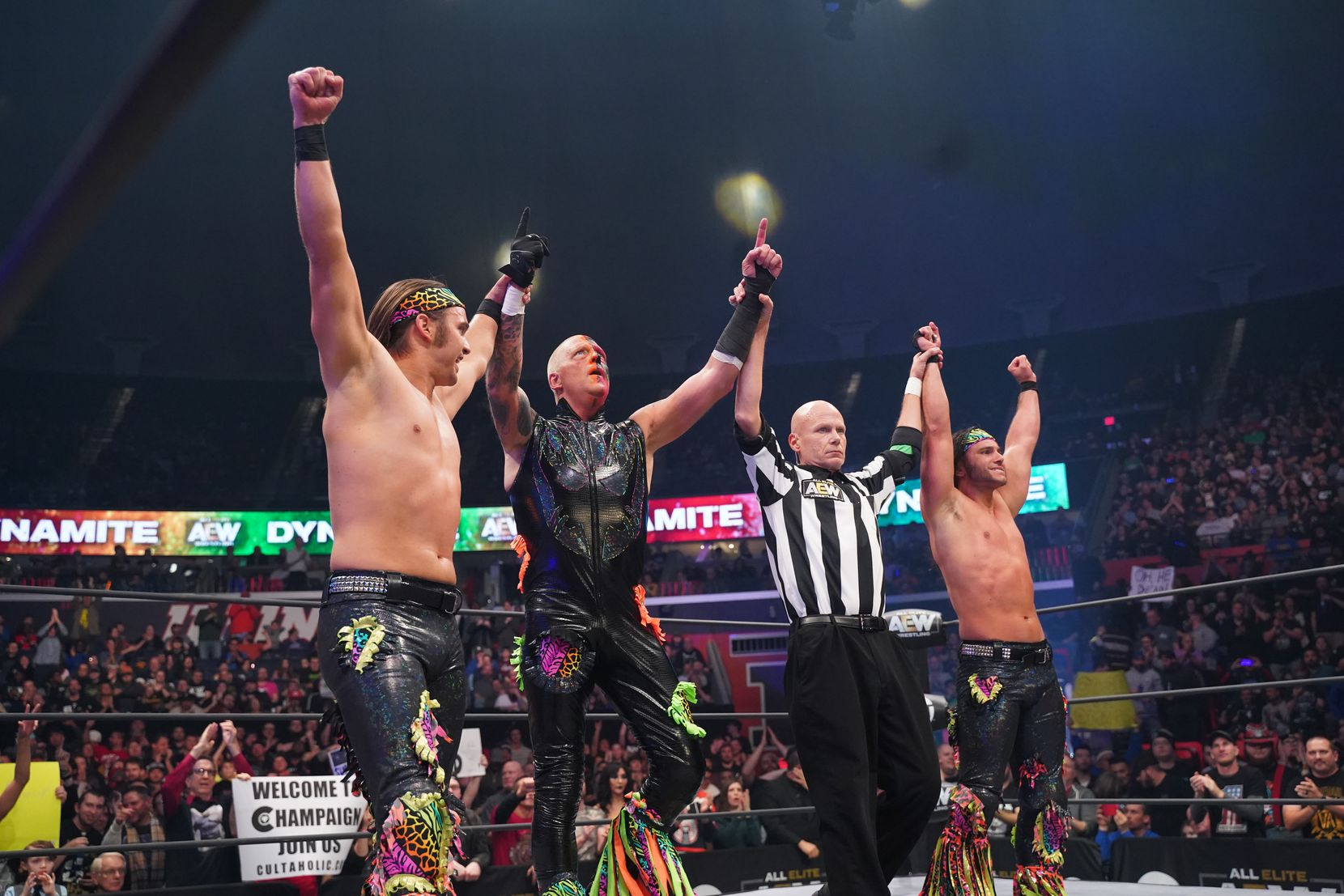 Dustin Rhodes celebrates with The Young Bucks after a victory on AEW Dynamite in Champaign, Illinois.