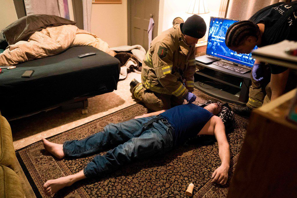 """Firefighter Jim Terrero (R) and Corey Joy, of the Manchester Fire Department, assess the condition of a 35-year-old man who had overdosed on heroin March 28, 2018 in Manchester, New Hampshire. The man was revived with two doses of Narcan. Tucked away in the corner of a US fire station are two plastic chairs, a tiny poster saying """"anyone, anytime, can recover,"""" and a poem in memory of a 20-year-old woman who fatally overdosed in 2016. The space is little more than a cubby hole, but has become a safe harbor for drug addicts in New Hampshire and symbol of hope in the US fight against the opioid crisis, a group of drugs, which like morphine, dulls pain and induces euphoria.   / AFP PHOTO / Don EMMERTDON EMMERT/AFP/Getty Images"""