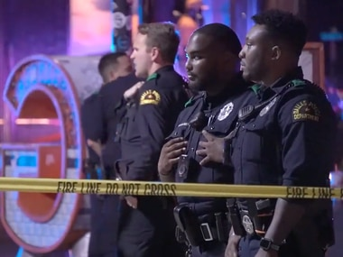 Dallas police officers survey the scene after multiple people were wounded in gunfire in Deep Ellum on Sunday, September 19, 2021.