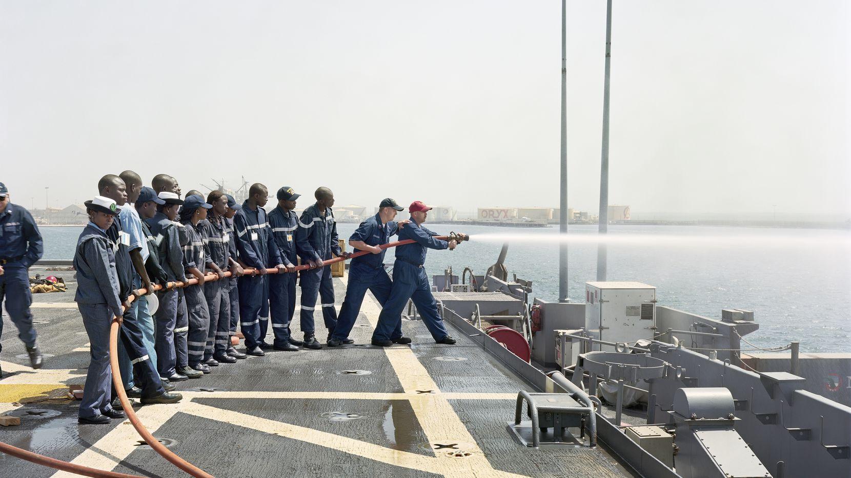 "Sailors train with a fire hose in An-My Lê's 2009 photograph ""Damage Control Training, USS Nashville, Dakar, Senegal."" (© An-My Lê. Courtesy of the artist and Marian Goodman Gallery, New York, Paris and London)"