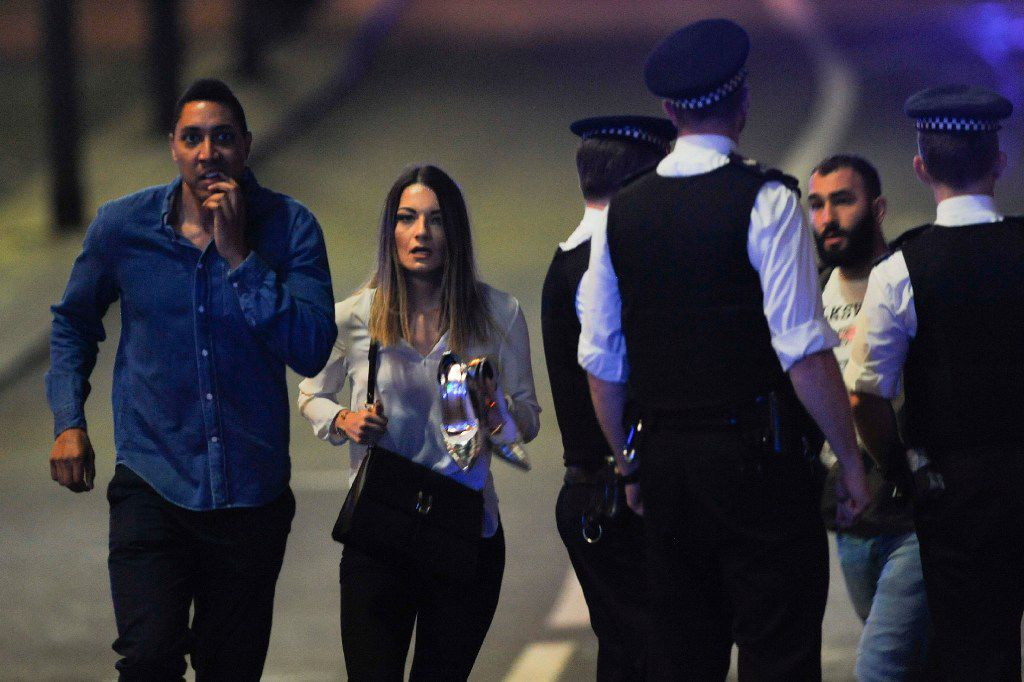 Members of the public leave the scene of a terror attack on London Bridge in central London on June 3, 2017.