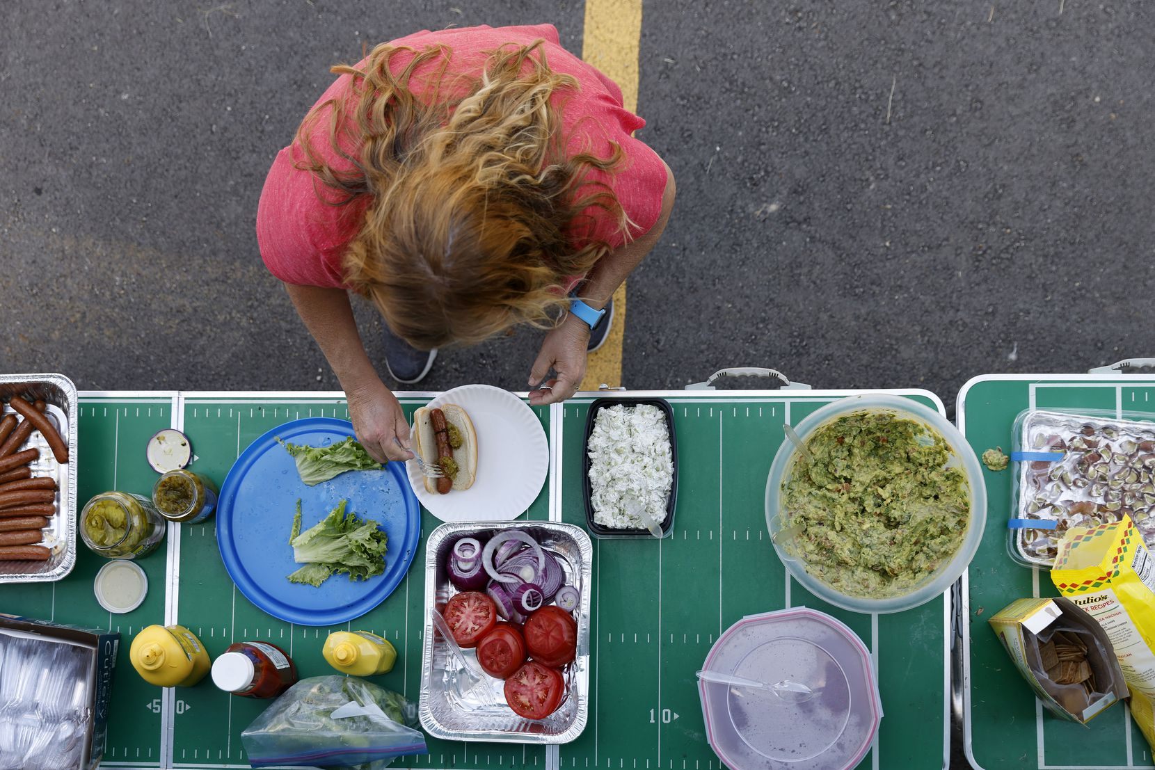 A Texas Rangers fan makes herself a lunch at an Opening Day tailgate party on private property outside of Globe Life Field in Arlington, Monday, April 5, 2021. The Rangers are facing the Toronto Blue Jays in the home opener. (Tom Fox/The Dallas Morning News)