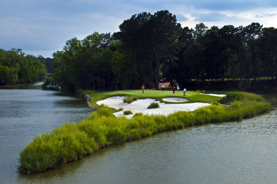 Golfers play the signature par 4, No. 15 green at Whispering Pines Golf Club in Trinity, TX.