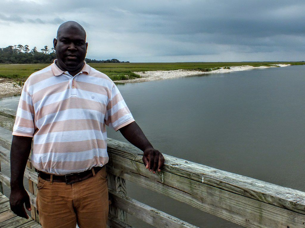 JR Grovner, a native of Georgia's Sapelo Island, stands on the pier where he greets guests for his daily tours.