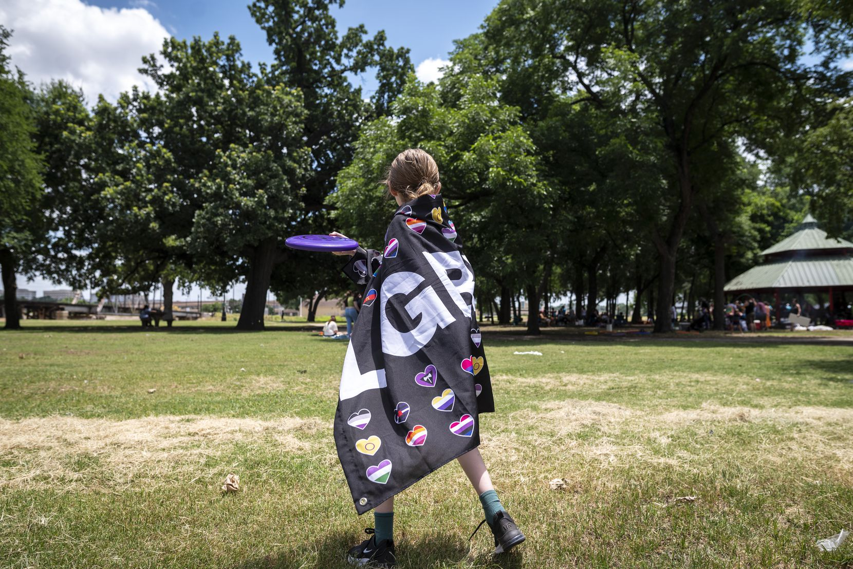 Alex Austin, 11, wears an LGBT flag while throwing Frisbee with her parents during the LGBTQ SAVES (Students, Allies, Volunteers, Educators, Support) Summer Camp CommUNITY Picnic at Trinity Park in Fort Worth on June 26.