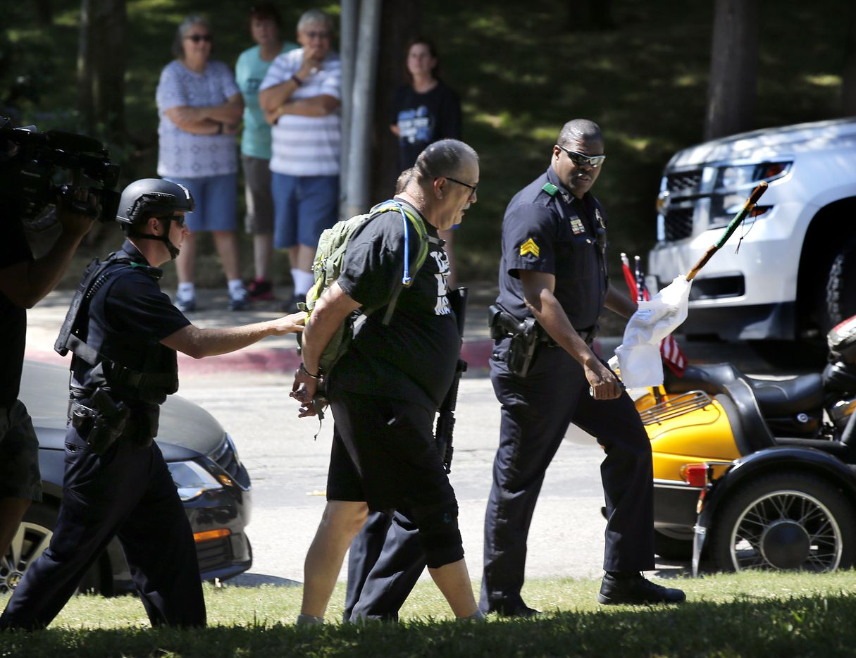 A man opposed to the rally was led away in handcuffs by Dallas police after a physical confrontation at the This Is Texas Freedom Force protest Saturday over removal of the Robert E. Lee statue from Lee Park in Dallas. The statue was removed from Lee Park on Thursday.