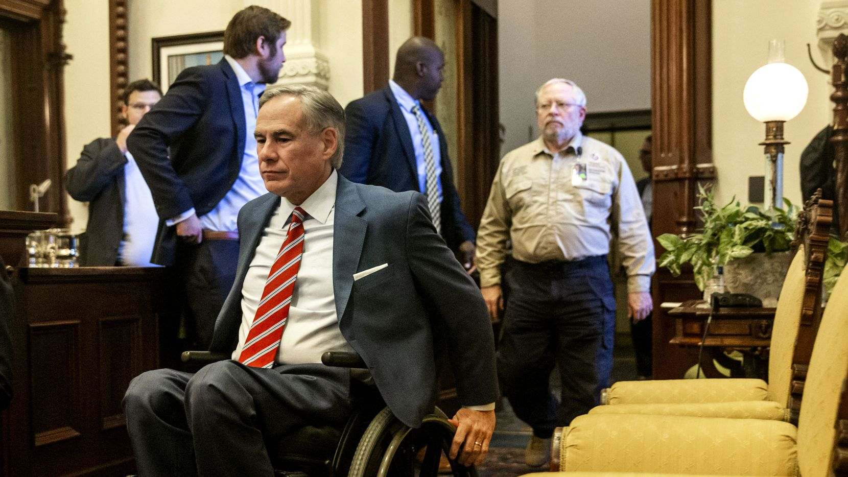 Gov. Greg Abbott, shown entering a May 18 press conference, was ridiculed -- both for his coronavirus policies and his use of a wheelchair -- in an expletive-laden tirade by two Empower Texans operatives that was mistakenly released with their podcast on June 19.
