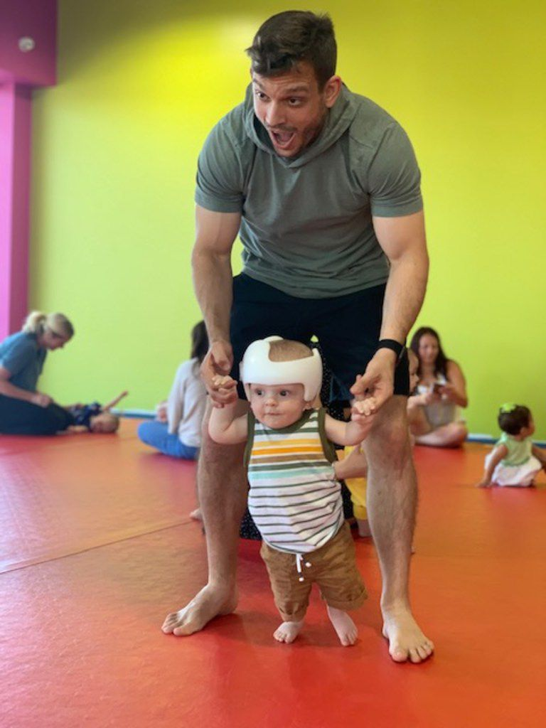 Ryan Layman helps his son, Rory, walk upright. Layman and his husband chose surrogacy in their family planning and ended up influencing a change in how Layman's employer, PwC, provides benefits like surrogacy reimbursement. Newborn Rory wears a helmet to reshape a flat spot on his head.