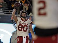 FILE - Oklahoma tight end Grant Calcaterra celebrates a touchdown catch in the second half of a game against West Virginia on Nov. 23, 2018, at Mountaineer Field in Morgantown, W. Va.