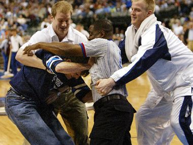 Mavericks  owner Mark Cuban fights with an actor/referee while Mavs' Evan Eschmeyer, right, moves in to restrain the two. The staged melee was Cuban playing a joke on fans during the New Orleans Hornets game at the AA Center.