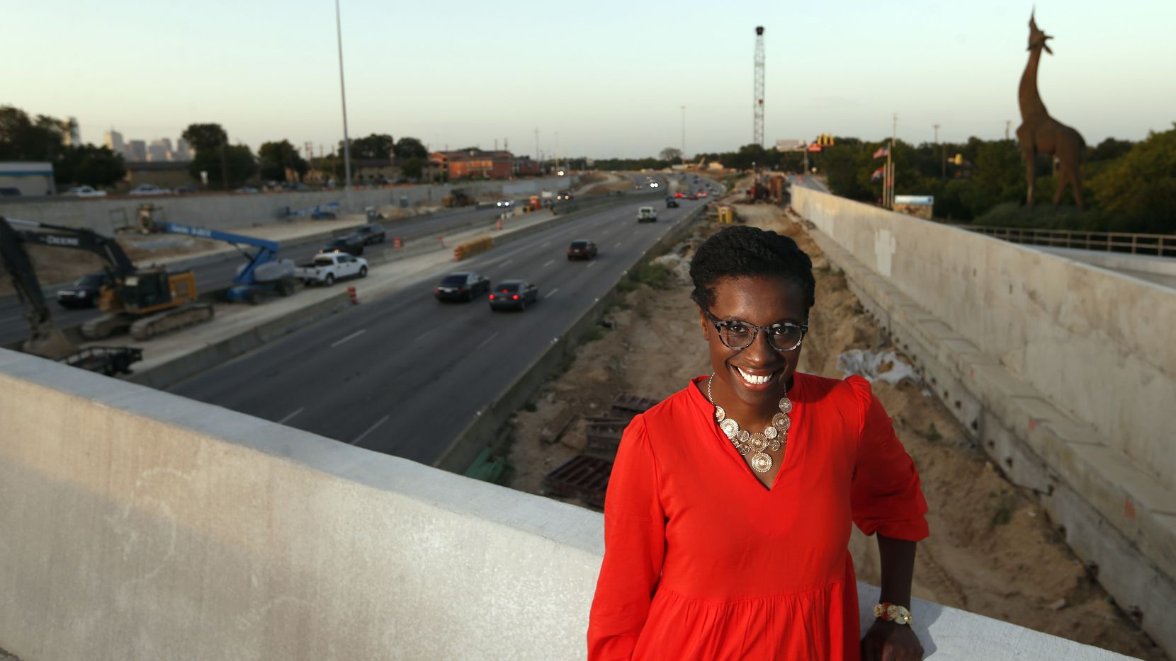 April Allen, the new president of the Southern Gateway Public Green Foundation, stands on the Marsalis Avenue bridge over I-35E with the Dallas Zoo and downtown in the distance. Behind her, the concrete skeleton of the Southern Gateway deck park is beginning to rise.