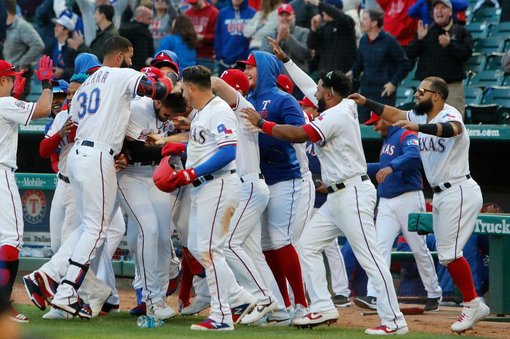 Texas Rangers Joey Gallo is mobbed by his teammates after scoring the game winning run during the ninth inning of a baseball game against the Chicago Cubs in Arlington,Texas, Sunday, March 31, 2019. The Rangers won 11-10. (AP Photo/LM Otero)