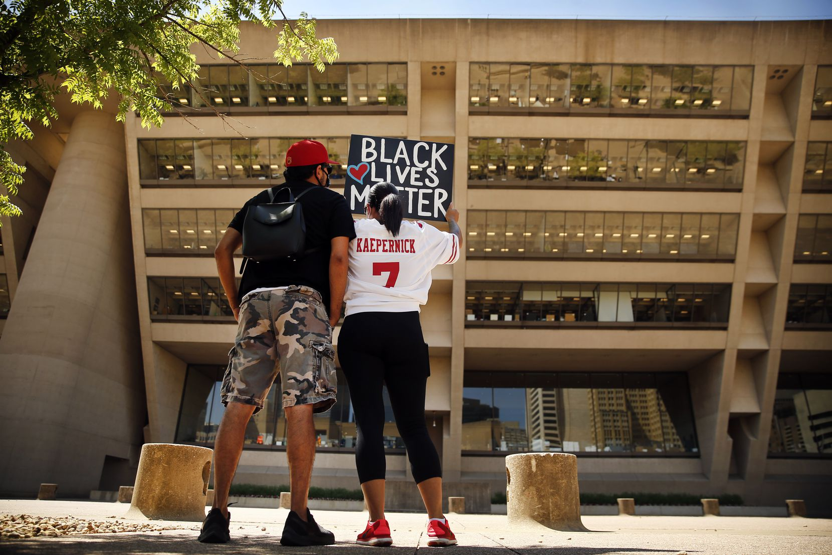 Protestors Xavier Reyes (left) and his girlfriend Aprille Peterson raise their Black Lives Matter painting toward Dallas City Hall during a Silent Protest and Mourning rally, Thursday, June 4, 2020. Aprille is wearing Xavier's Colin Kaepernick jersey, one he got before the kneeling protest and has worn ever since. No one spoke as they stood in solidarity with signs, protesting the in-custody death of George Floyd in Minneapolis.