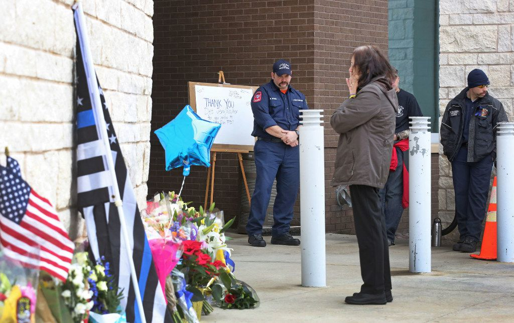 Passers-by stop at the memorial outside the Little Elm Police Department on Wednesday. (Louis DeLuca/Staff Photographer)