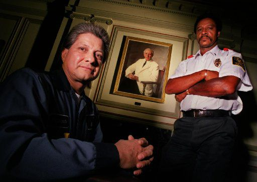 Maintenance man Fernando Ramirez and security guard Jonas Griffin stand in front of a portrait of Karl Hoblitzelle in a boardroom of the Majestic Theatre. Ramirez said he has seen the ghost several times and Griffin said he sees inexplicable happenings such as strange elevator activity .