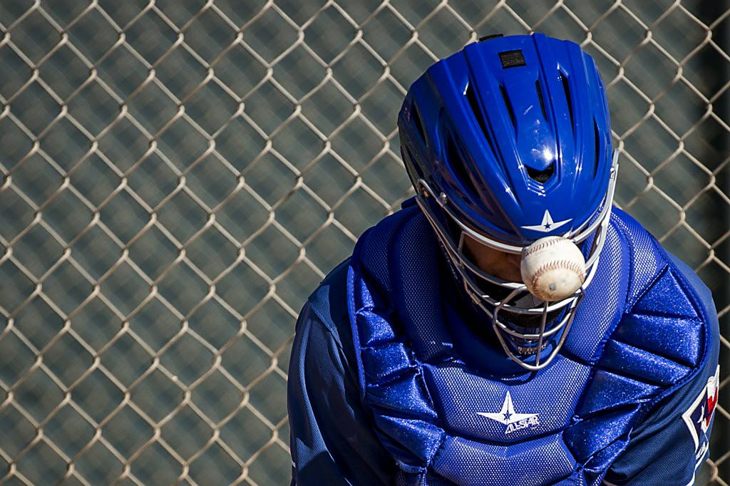 Texas Rangers minor league catcher Jose Trevino has a ball bounce off his mask during a drill tduring a spring training workout at the team's training facility on Saturday, Feb. 20, 2016, in Surprise, Ariz. (Smiley N. Pool/The Dallas Morning News)