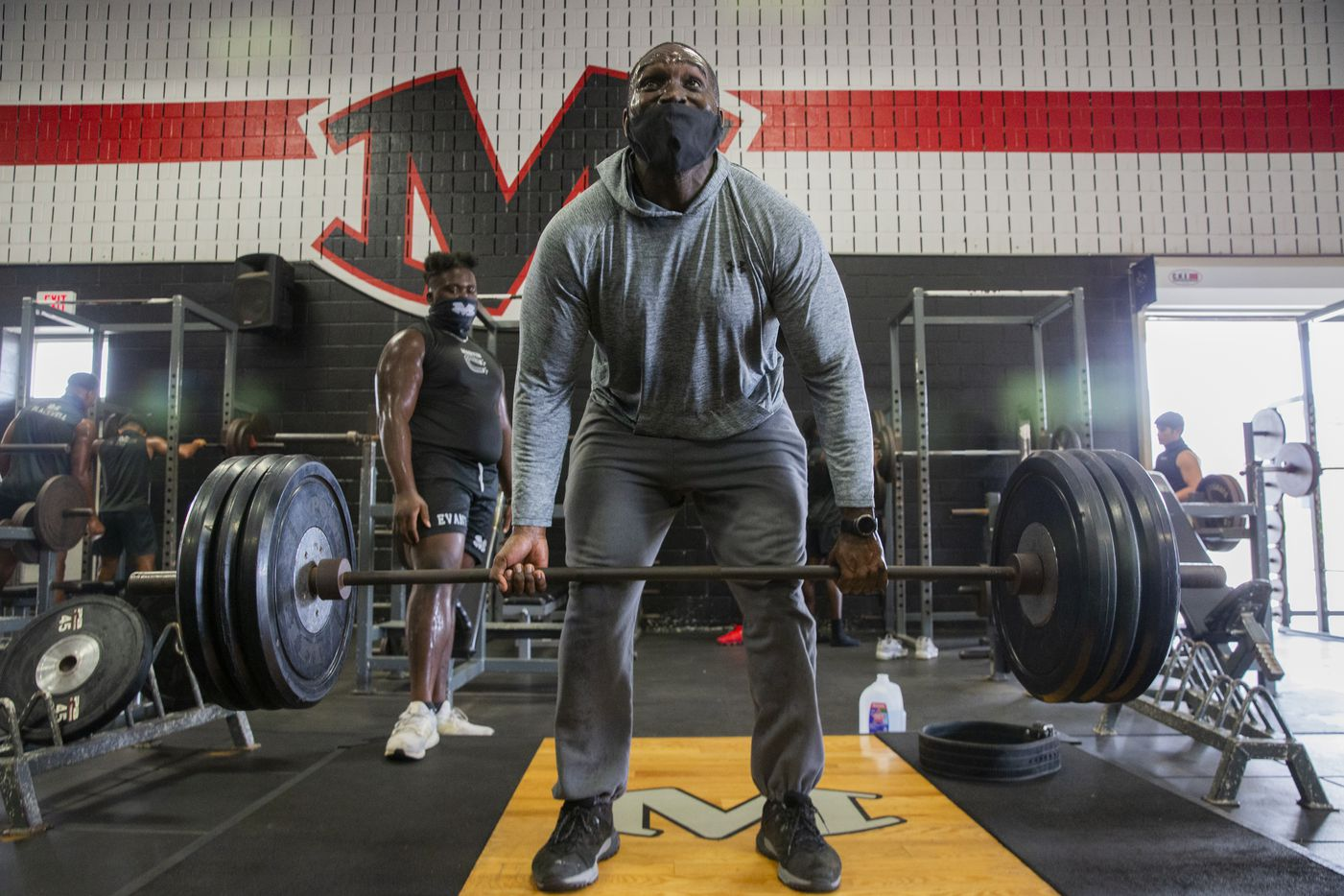 """Homicide Sergeant Brian Jones from the Arlington Police Department works out with Arlington Martin football players at their gym as part of the """"Coach 5-0"""" program on Monday, Sept. 21, 2020 in Arlington. (Juan Figueroa/ The Dallas Morning News)"""