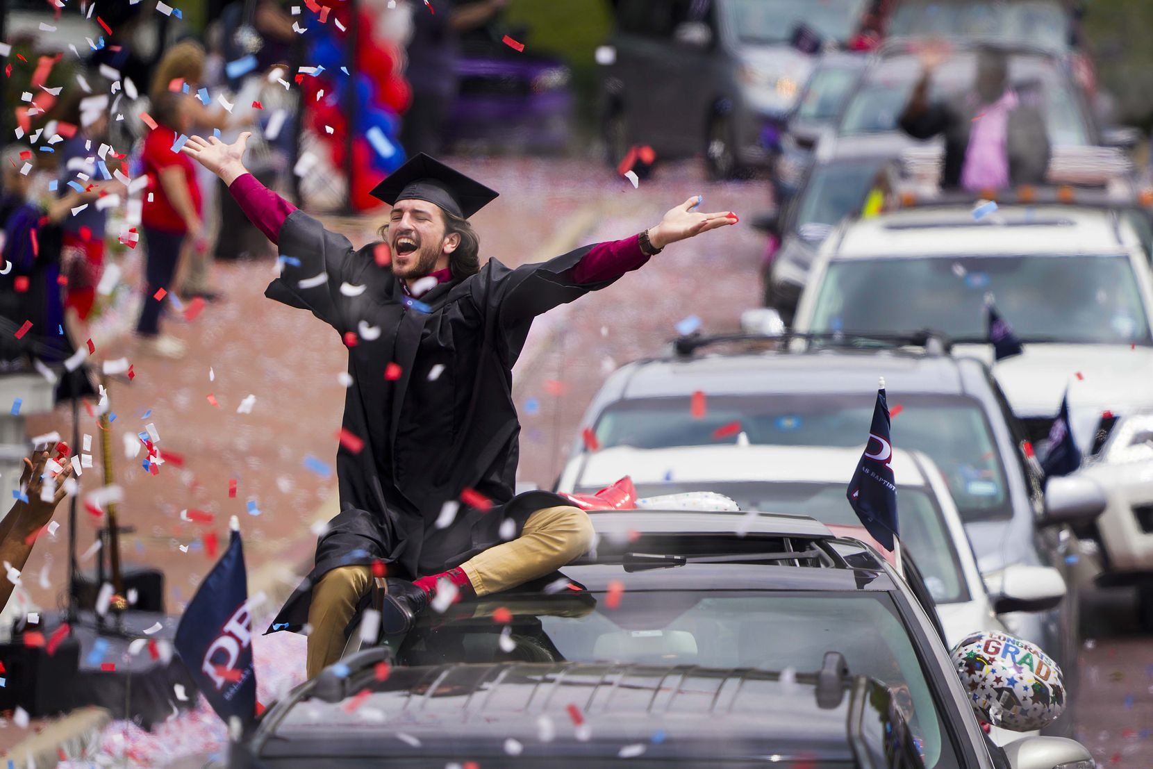 Graduate William Santini celebrated as confetti fell during a commencement car parade at Dallas Baptist University on May 15, 2020. DBU graduates moved by car through the campus and had their names called as they passed Pilgrim Chapel before proceeding onward to collect diplomas. Approximately 350 graduates passed through the campus in a parade of approximately 600 cars.