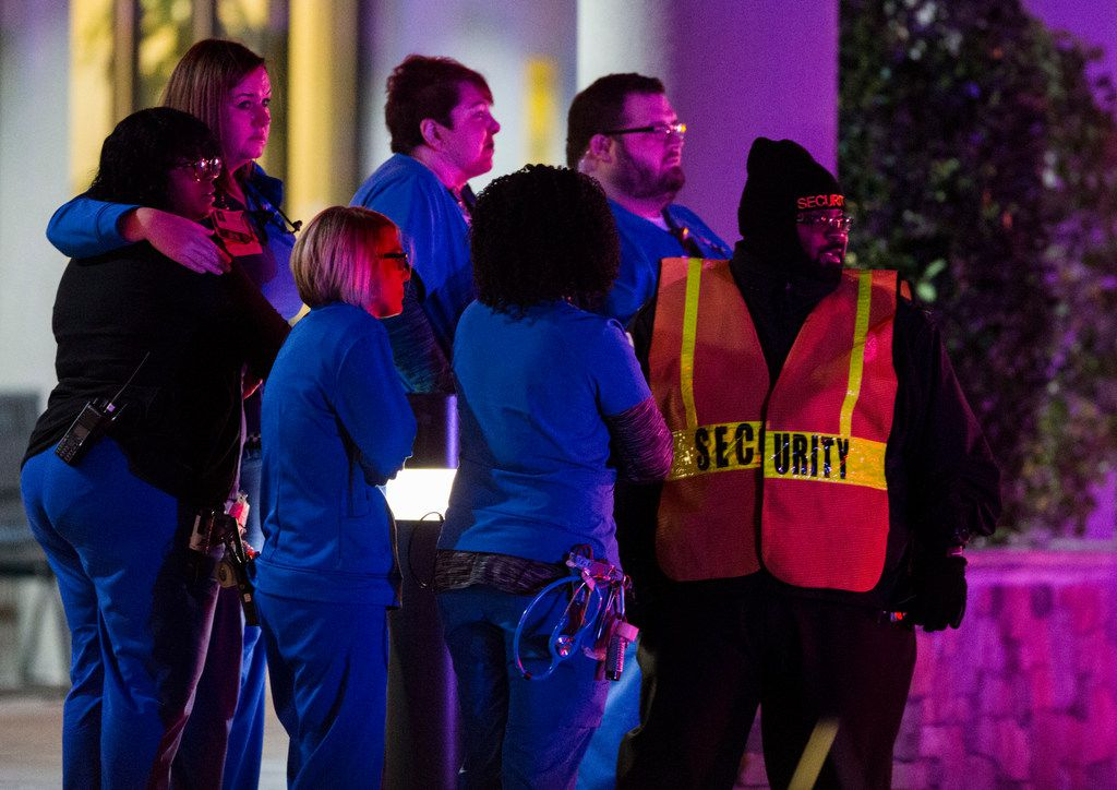 Medical personnel and a security officer watch as police officers leave the emergency room at Medical City Plano hospital in Plano, Texas after a Richardson, Texas police officer was shot and killed on Wednesday, February 7, 2018 at an apartment complex in Richardson.