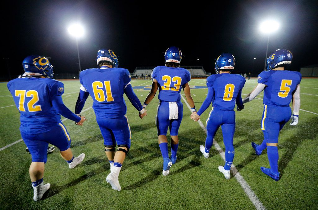 Community High football captains (from left) Eli Hartley, Kannon Marrow, Sean Outlaw, Parker Simpson, and Tyson Neighbors walk hand-in-hand to the coin toss with Dallas Roosevelt at Community ISD Stadium in Nevada, Texas, Friday, November 8, 2019. Roosevelt captains gave them plants before the toss. Community was playing with heavy hearts after four of their classmates were killed in a tragic vehicle accident earlier this week. (Tom Fox/The Dallas Morning News)
