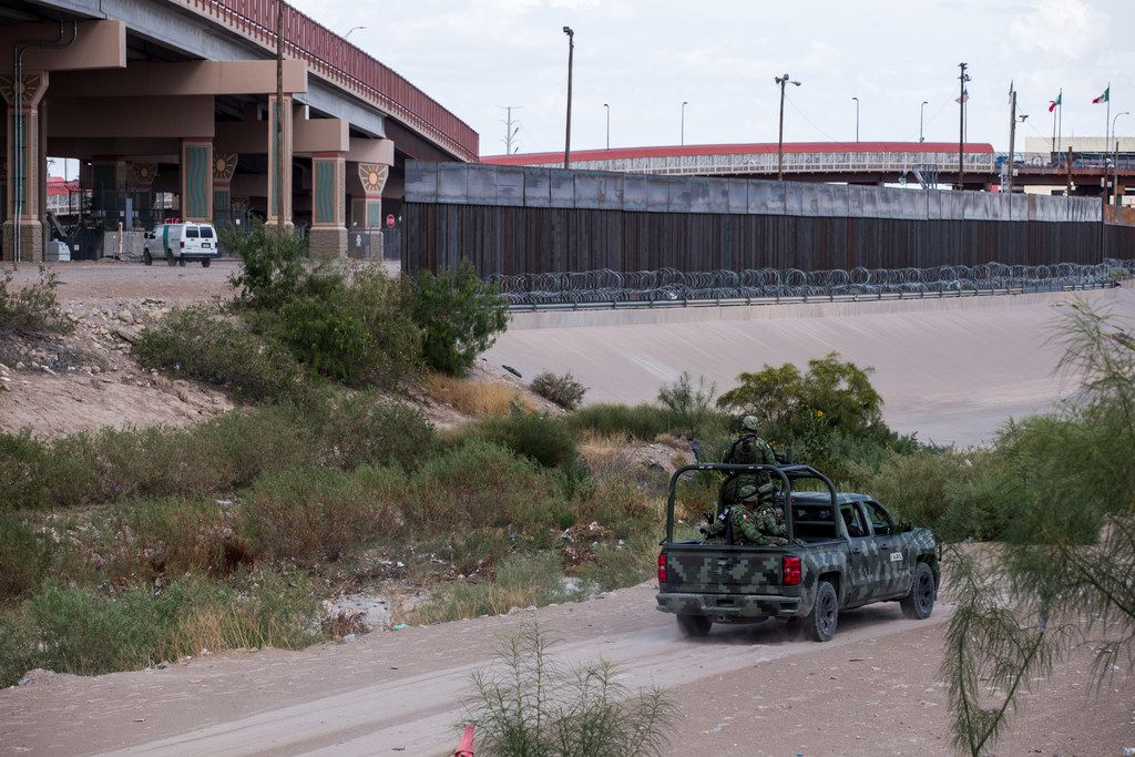 The Mexican National Guard, right, patrols an area along the Rio Grande directly across from a section of border fencing between the U.S. and Mexico on Aug. 1, 2019.