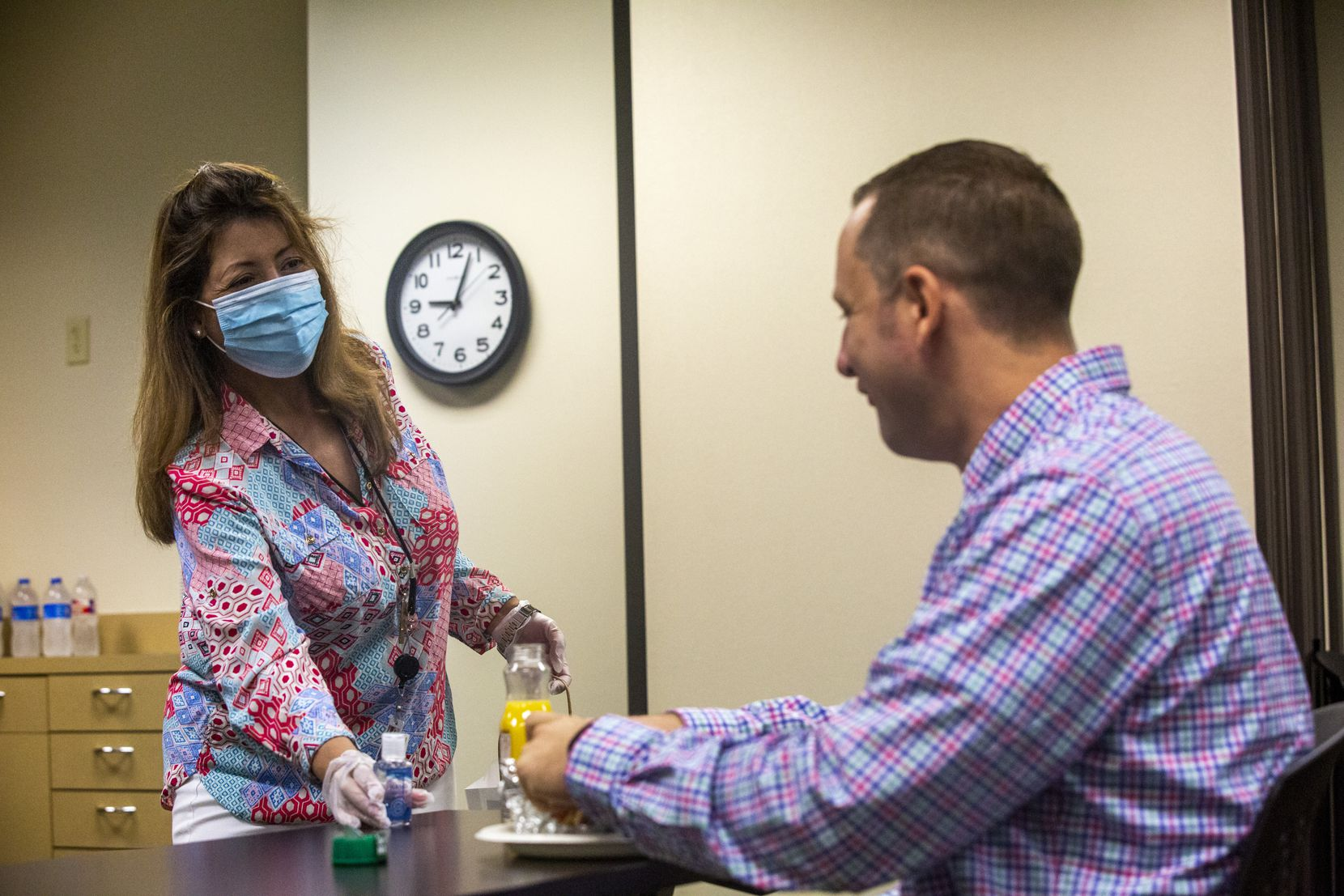 Administrative assistant Robbie Marquez (left) hands a hand sanitizer bottle to new hire and quality assurance analyst Daniel Stirrat during a meet-and-greet breakfast with new company hires at the VPay office in Plano.