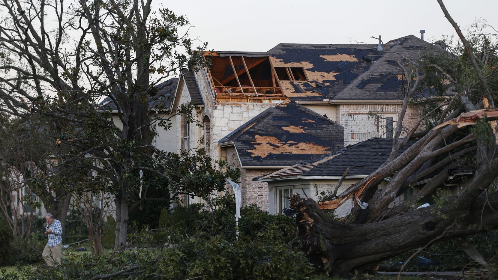 As the sunrises, homeowners emerge to survey damage from a tornado the night before near Northcrest Road and Crestline Avenue in Dallas on Sunday, Oct. 21, 2019.