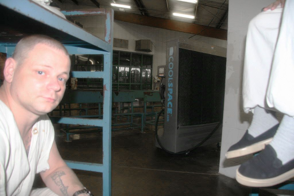 Inmates sit near a temporary cooling fan in June 2014 at the Texas Department of Criminal Justice's Holliday Unit near Huntsville.