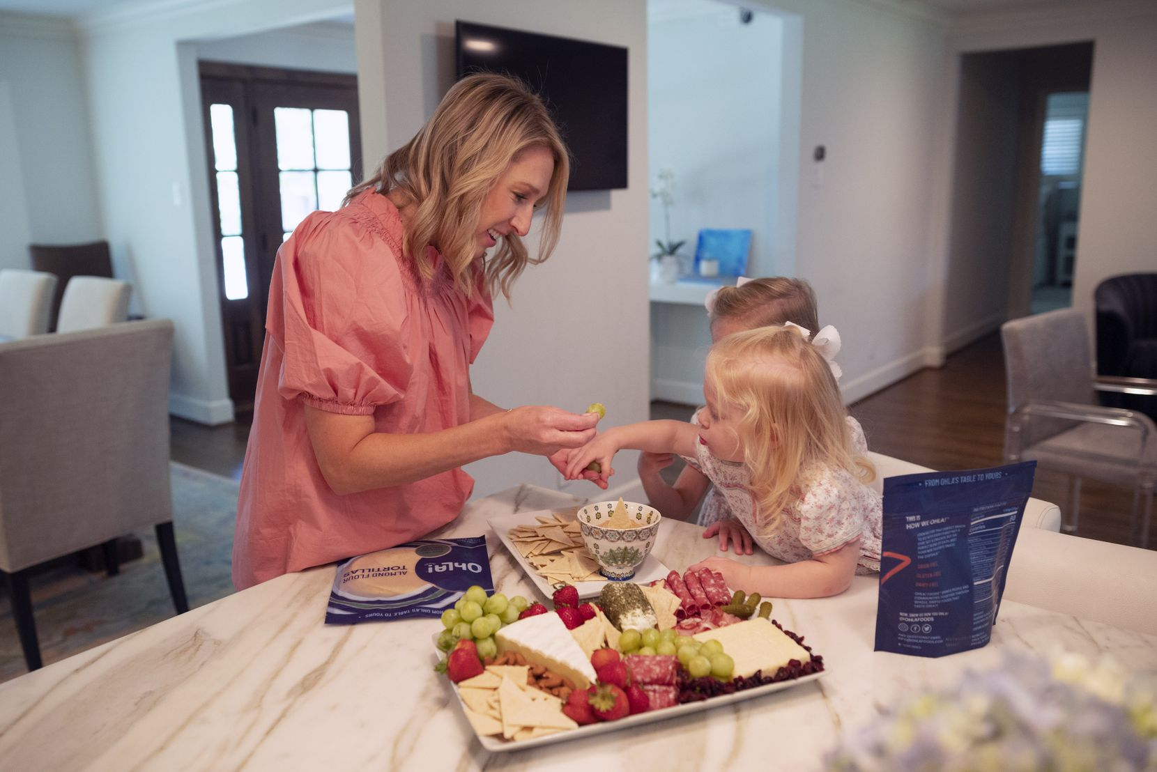 Lauren Schwalb, founder of Ohla! Foods, feeds a snack of ChipOhla! chips to her children Olivia, 4, and Hadley, 2, right, at her home in Dallas.