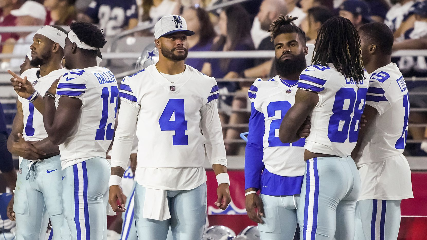 Dallas Cowboys quarterback Dak Prescott (4) watches from the sidelines with wide receiver Cedrick Wilson (1), wide receiver Michael Gallup (13), running back Ezekiel Elliott (21), wide receiver CeeDee Lamb (88) and wide receiver Amari Cooper (19) during the second quarter of an NFL football game against the Arizona Cardinals at State Farm Stadium on Friday, Aug. 13, 2021, in Glendale, Ariz.
