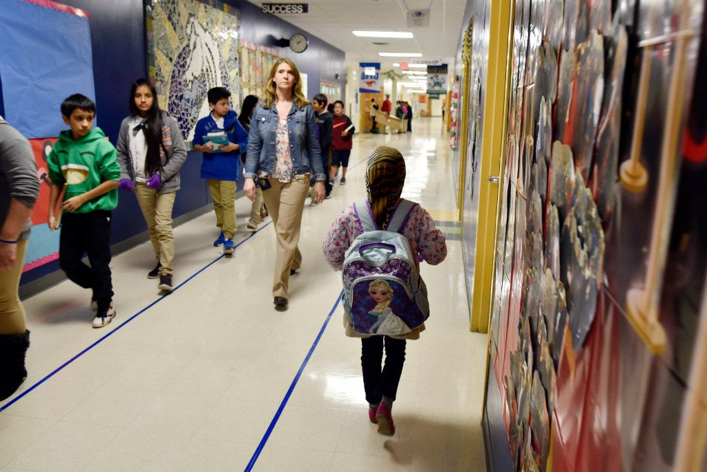 First-grader Halima Hassan walks through a hallway to her main classroom after working with a volunteer on her English reading skills at Lee A. McShan Jr. Elementary School in Dallas. (2016 File Photo/Ben Torres)