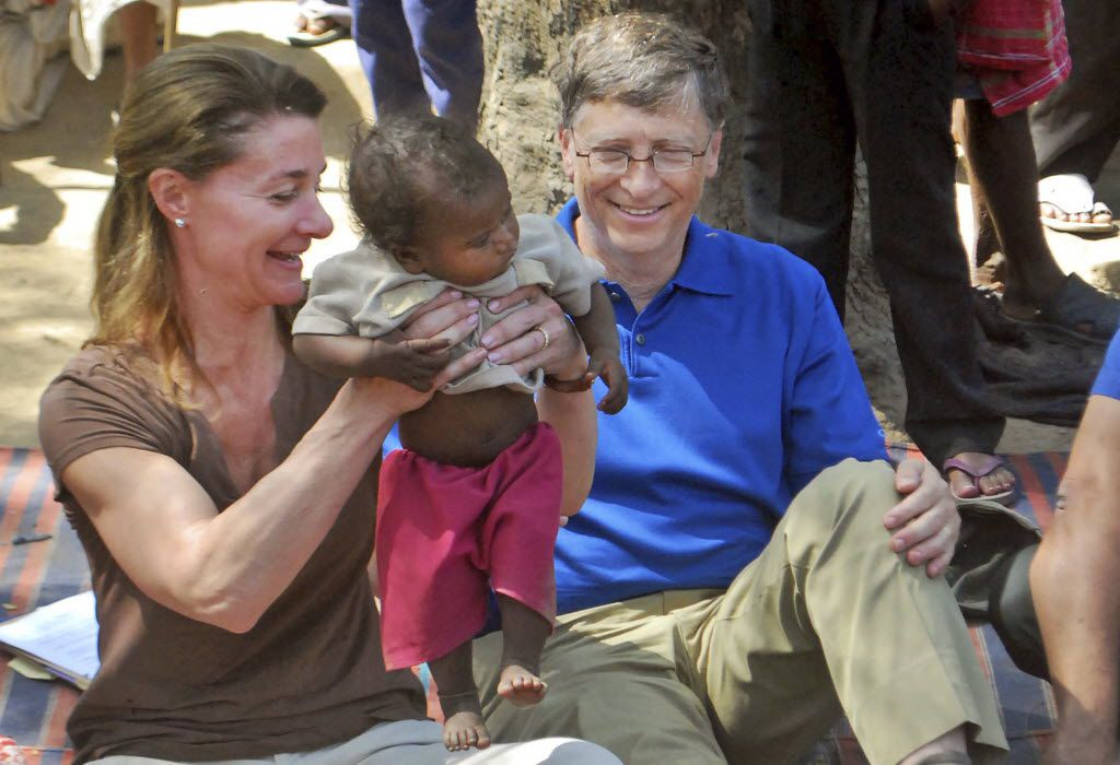 Melinda Gates and her husband, Microsoft founder Bill Gates, play with a child in Jamsot Village near Patna, India.