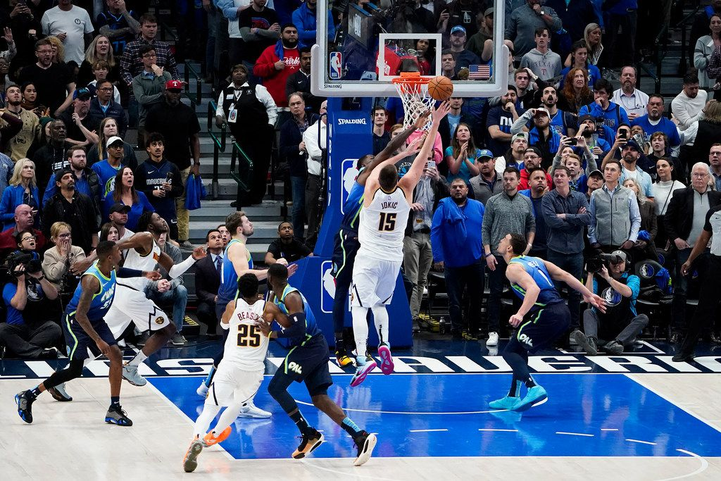 FILE - Nuggets center Nikola Jokic (15) scores over Mavericks forward Dorian Finney-Smith (10) with 7.9 seconds left to give Denver a 107-106 victory at American Airlines Center on Wednesday, Jan. 8, 2020, in Dallas.