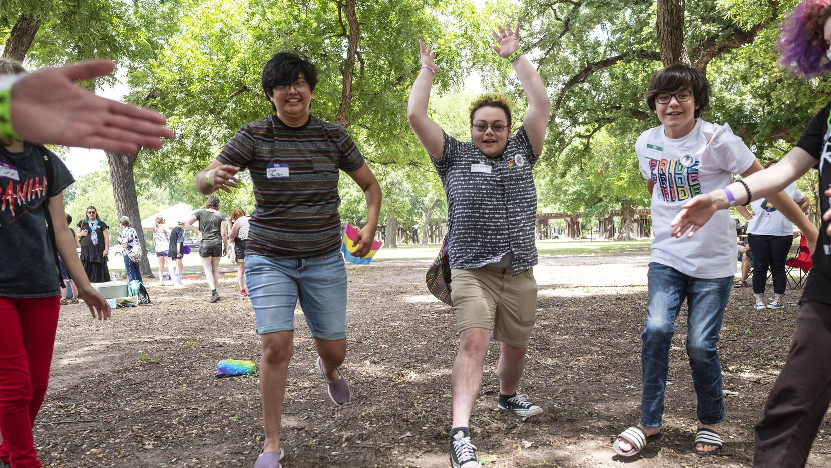 Lyssa Alvarado, 23, left, Kairo Donahue, 17, and Taylor Masterson, 13, right, play a game during the LGBTQ SAVES (Students, Allies, Volunteers, Educators, Support) Summer Camp CommUNITY Picnic at Trinity Park in Fort Worth on June 26.