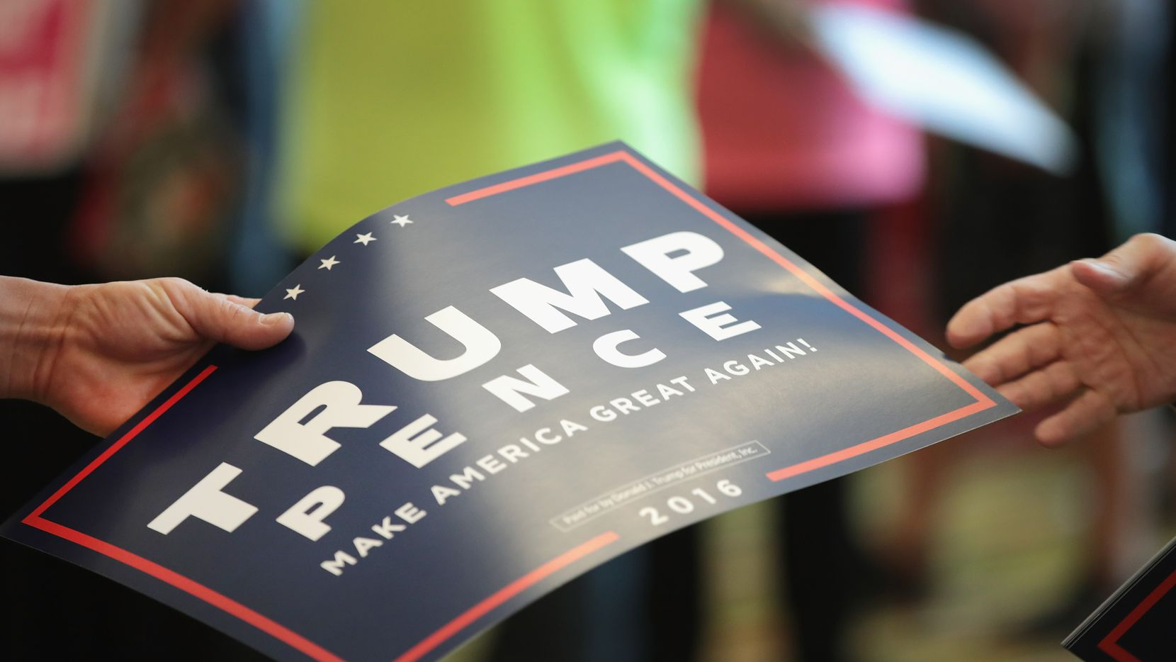 GREEN BAY, WI - OCTOBER 17:  A volunteer hands out signs before the start of a campaign rally with Republican presidential nominee Donald Trump at the KI Convention Center on October 17, 2016 in Green Bay, Wisconsin. Trump will square off with democratic rival Hillary Clinton for a final debate before the election on October 19 in Las Vegas.  (Photo by Scott Olson/Getty Images)