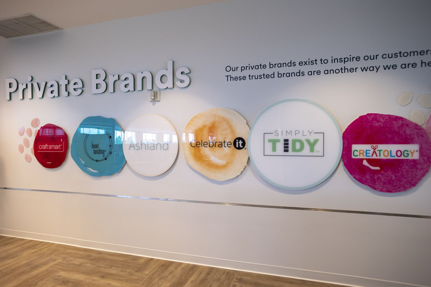 Logos from some of the private brands owned by Michaels are on display at the company's new headquarters in Irving.