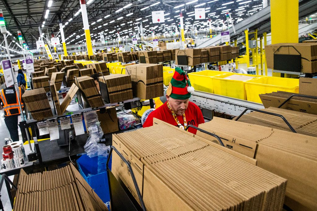 Donning an elf's hot, Jeffrey Tucker fills a box with air bags to cushion packages.